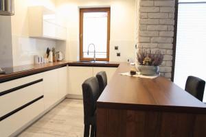 Zbliżenie na blat kuchenny połączony ze stołem barowym pokrytym okleiną z naturalnego drewna.
