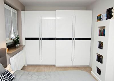 Widok na szafy na wymiar do sypialni w białym kolorze z czarnym pasem.