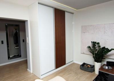 Szafa w zabudowie do salonu z biało - drewnianymi drzwiami przesuwanymi.