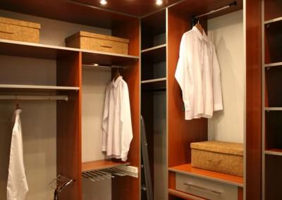 Widok górnej części garderoby z półkami na ubrania z oświetleniem.