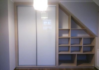 Biała szafa z drzwiami przesuwanymi oraz półkami we wnętrzu na poddaszu.