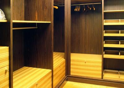 Pojemna garderoba na wymiar w mieszanych odcieniach drewna.