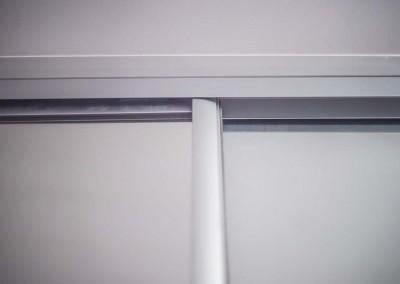 Górna szyna dla drzwi przesuwnych w szafie z lustrem na wymiar.