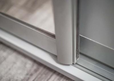 Precyzyjne wykończenie drzwi z lustrem w szafie na wymiar.
