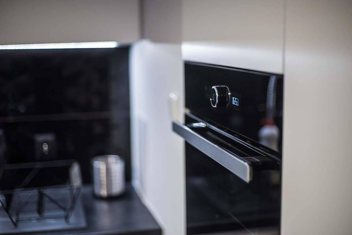 Zdjęcie w zbliżeniu na precyzyjne zamontowanie sprzętu AGD w kuchni na wymiar.