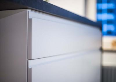 Zdjęcie w zbliżeniu na staranne wykończenie szuflad w kuchni na wymiar.