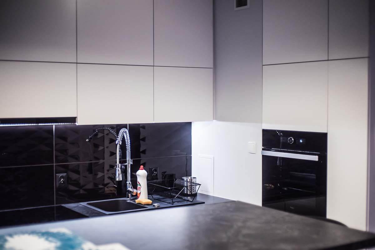 Górne szafki kuchni oraz część prawej ściany z zabudową piekarnika.